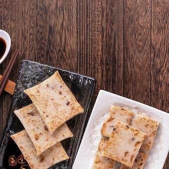 Heerlijke raapcake, chinese traditionele radijscake in restaurant met sojasaus voor nieuwjaarsgerechten, close-up, kopieerruimte, bovenaanzicht, plat gelegd.