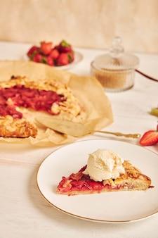 Heerlijke rabarber aardbeien gallate cake met ingrediënten op een witte tafel