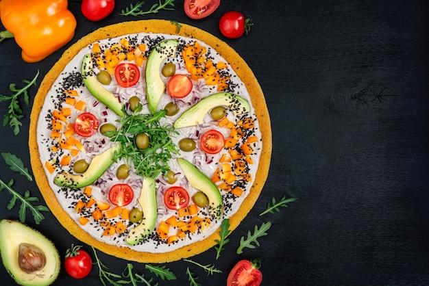 Heerlijke rauwe pizza met avocado, peper, rucola, olijven en tomaten op een zwarte achtergrond. bovenaanzicht.