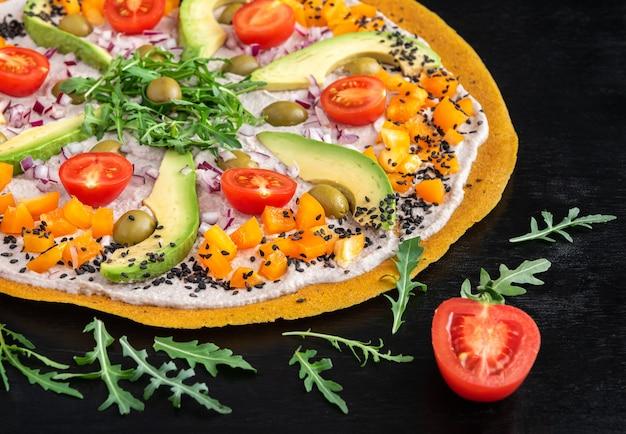 Heerlijke rauwe pizza met avocado, peper, rucola, olijven en tomaten op een zwarte achtergrond.