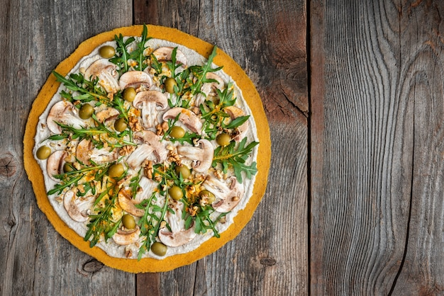 Heerlijke rauwe pizza met champignons, walnoten, rucola en groene olijven. bovenaanzicht.