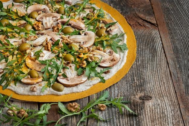 Heerlijke rauwe pizza met champignons, walnoten, rucola en groene olijven.