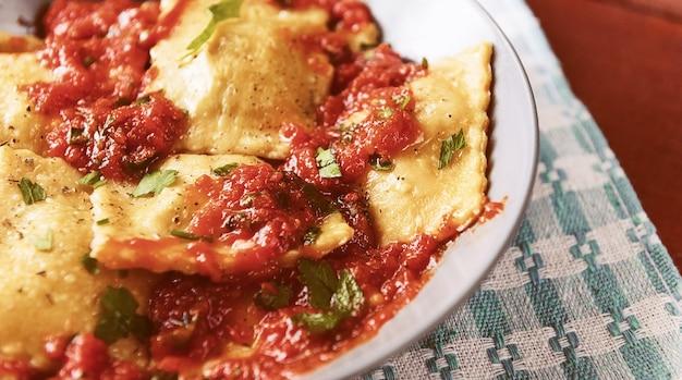 Heerlijke ravioli met tomatensaus in een bord op een houten ondergrond