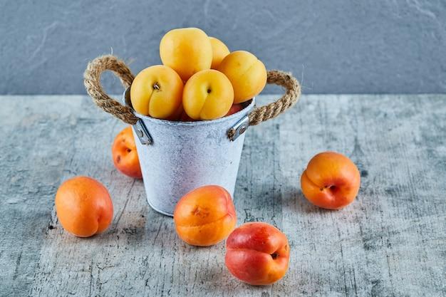 Heerlijke rijpe abrikozen in ijzeren emmer met nectarines op marmeren oppervlak