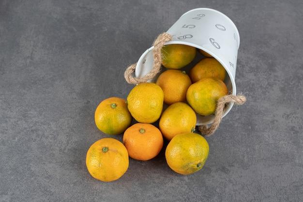 Heerlijke rijpe mandarijnen uit emmer op marmeren achtergrond. hoge kwaliteit foto