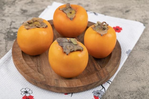 Heerlijke rijpe persimmonvruchten die op houten plaat worden geplaatst