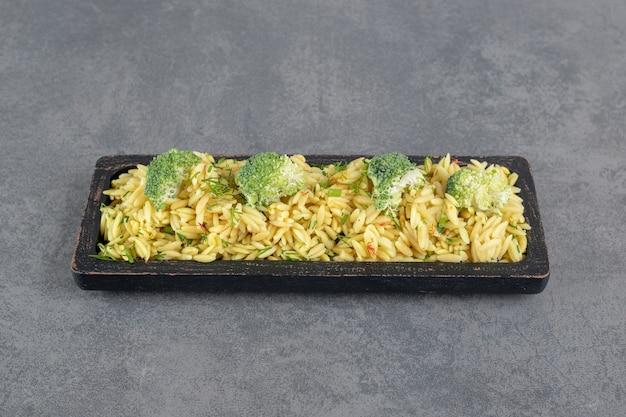 Heerlijke rijst met broccoli op zwarte plaat. hoge kwaliteit foto