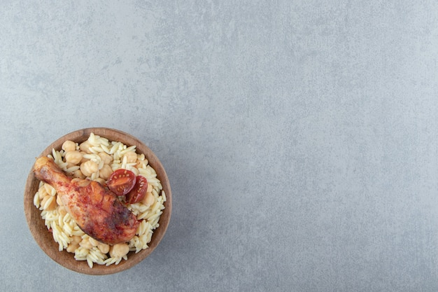 Heerlijke rijst met kikkererwten en kippenpoot in houten kom.
