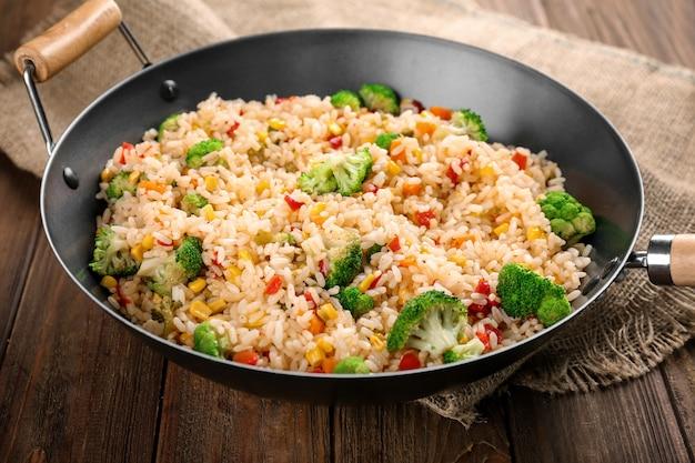 Heerlijke rijstpilaf met broccoli in wok op houten lijst