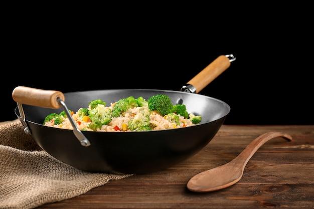 Heerlijke rijstpilaf met broccoli in wok op houten tafel