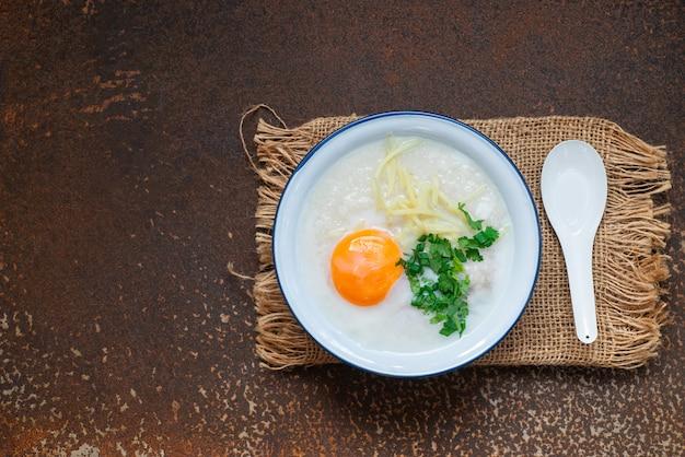 Heerlijke rijstsoep met vlees, ei en kruiden op roestige metaalmuur met exemplaarruimte, heet voedsel en gezond maaltijdconcept