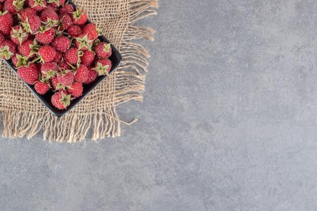 Heerlijke rode frambozen op zwarte plaat. hoge kwaliteit foto