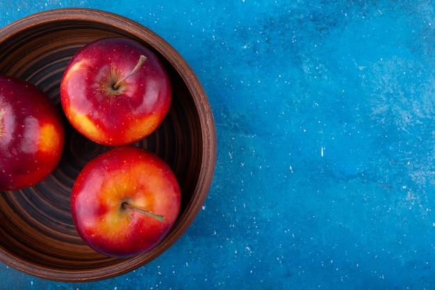Heerlijke rode glanzende appels die in houten kom worden geplaatst.