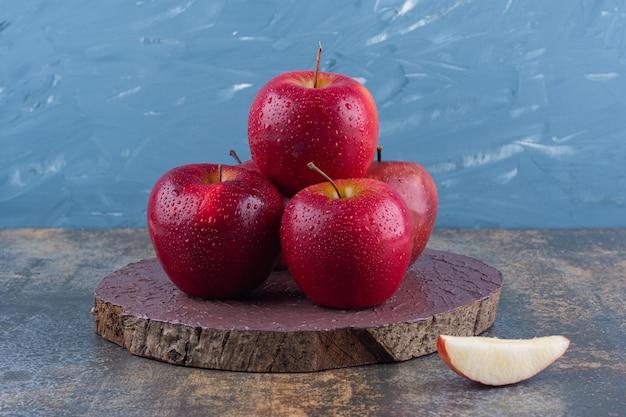 Heerlijke rode glanzende appels die op een houten bord worden geplaatst.