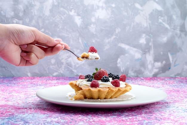 Heerlijke romige cake met verschillende verse bessen in plaat op helder licht bureau, bessenfruit vers zuur