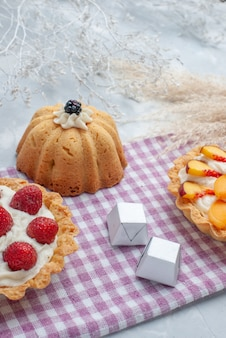 Heerlijke romige cakes met gesneden fruit, samen met chocoladesuikergoed en thee op licht bureau, cake, koekjes, zoete room, bak thee