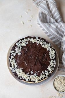 Heerlijke romige cheesecake gedecoreerd met chocoladeglazuur en amandel, licht betonnen oppervlak
