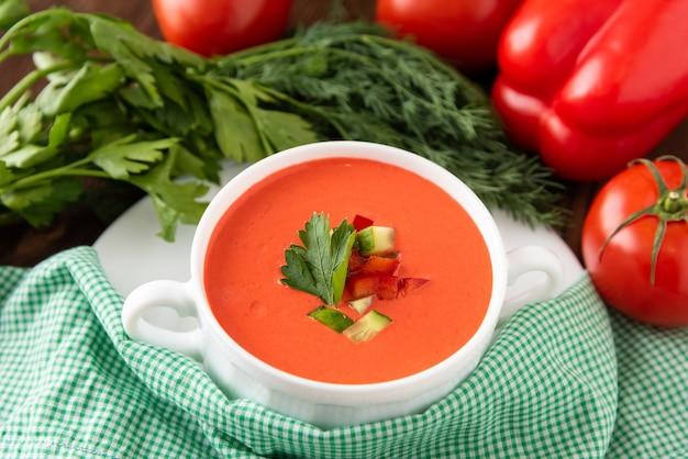 Heerlijke roomsoep van tomaten op een houten achtergrond met kruiden en croutons. in een soepkom.