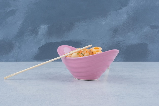 Heerlijke roze plaat met macaroni en eetstokjes op donkere ondergrond