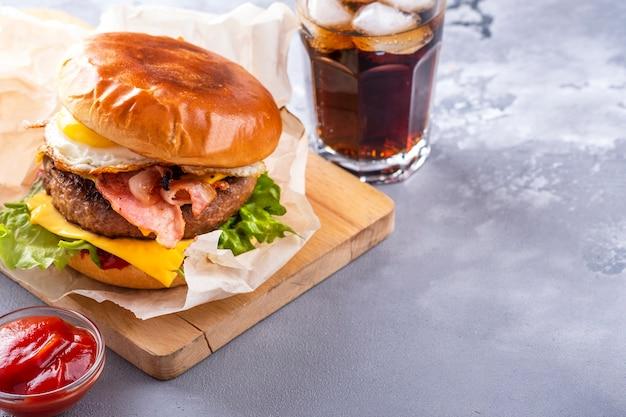 Heerlijke rundvleesburger geserveerd met ketchup en drank. fast food. tekstruimte.