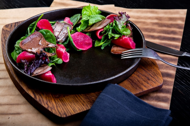 Heerlijke rundvleestong met spinazie en rode biet in restaurant