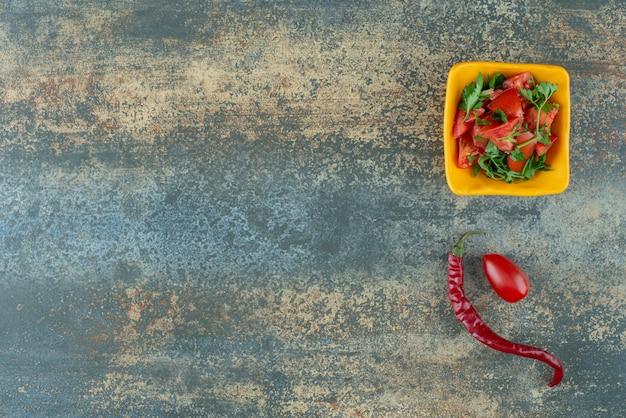 Heerlijke salade in gele plaat met peper en tomaat op marmeren achtergrond