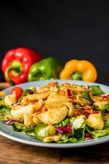 Heerlijke salade met kip; noten; en groenten op bureau tegen zwarte achtergrond