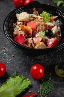 Heerlijke salade met kip, olijven en verse kruiden, een frisse salade op het menu van een fastfoodrestaurant op een donkere stenen tafel. gezonde optie van fast food.