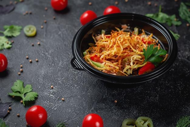 Heerlijke salade met tomaten, geroosterde aardappelen, tomaten en verse kruiden, een frisse salade op het menu van een fastfoodrestaurant op een donkere stenen tafel. gezonde optie van fast food.