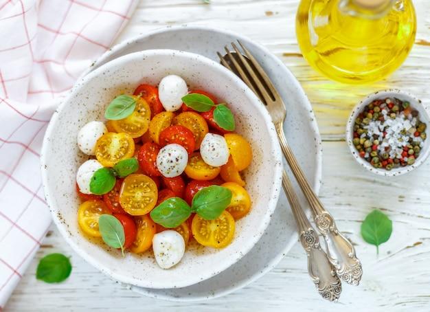 Heerlijke salade van gele en rode kerstomaten, mozzarella, basilicum, kruiden. caprese