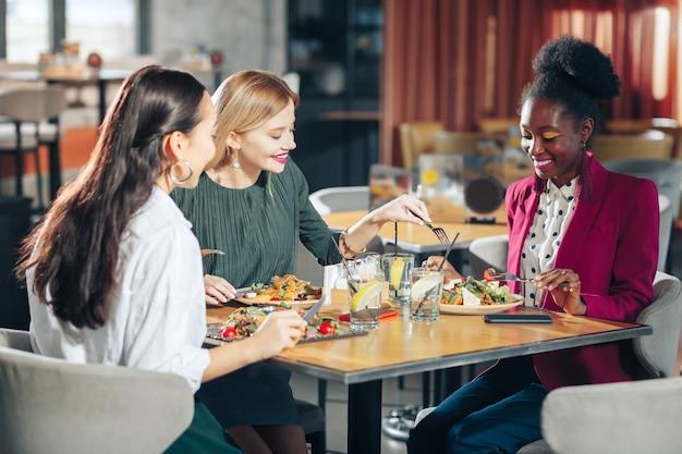 Heerlijke salades proberen drie beste vrienden voelen zich grappig terwijl ze heerlijke salades van elkaar proberen in restaurant