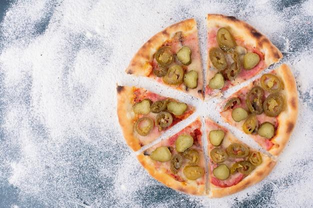 Heerlijke salamipizza met jalapenos op marmer.