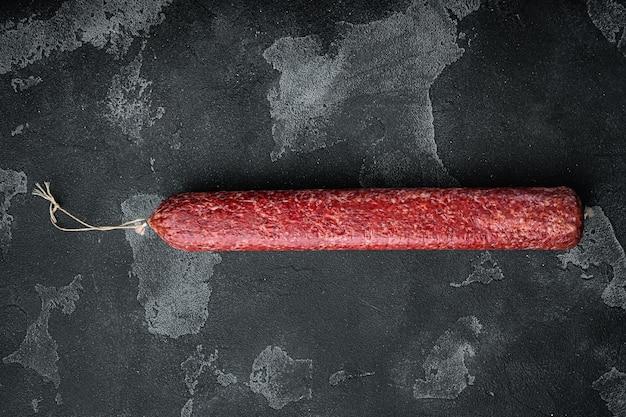 Heerlijke salamiworstset, op zwarte donkere stenen tafel, bovenaanzicht plat gelegd