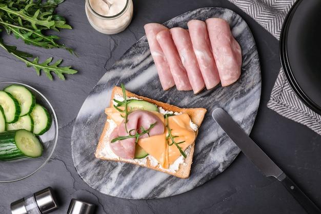 Heerlijke sandwich geserveerd op zwarte tafel, plat gelegd