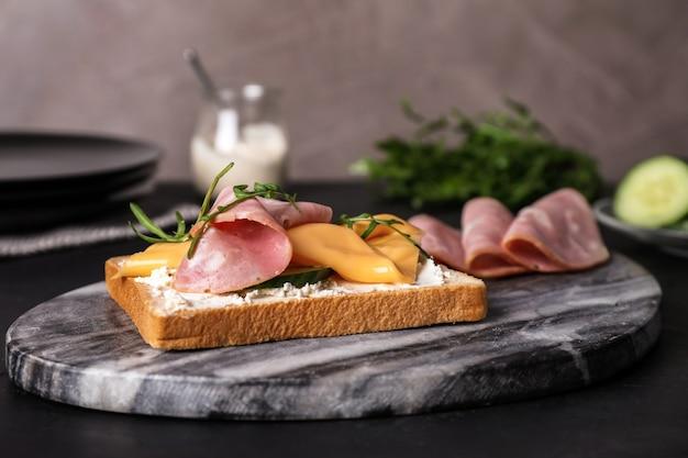 Heerlijke sandwich met ham op zwarte tafel