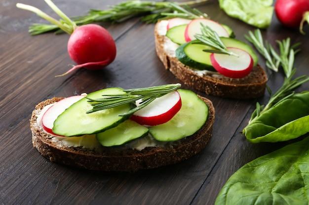 Heerlijke sandwiches met groenten en greens op tafel close-up