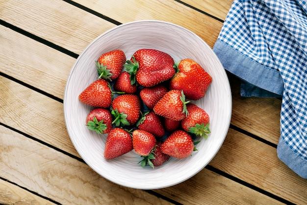 Heerlijke sappige aardbeien op de plaat met houten achtergrond.