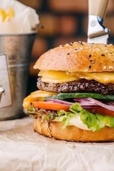 Heerlijke sappige cheeseburger van dichtbij van brioche bun. rundvlees, kaas, ui, tomaat, komkommer, saus, sla, stekmes en patat
