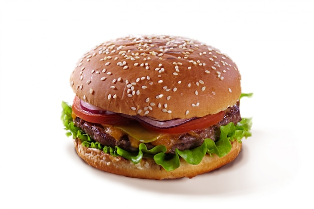 Heerlijke sappige hamburger met tomaten, kruiden, kaas en vlees geïsoleerd op een witte achtergrond. smakelijke hamburger die op wit met sesam wordt geïsoleerd.