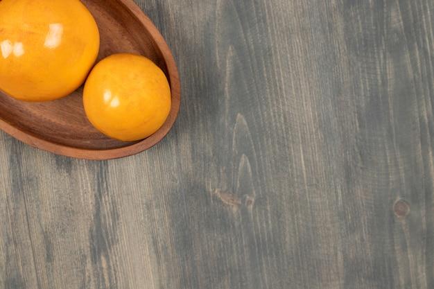 Heerlijke sappige kaki op een houten bord. hoge kwaliteit foto