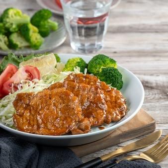 Heerlijke sappige karbonades met groentenmaaltijd in een plaat op eettafel.