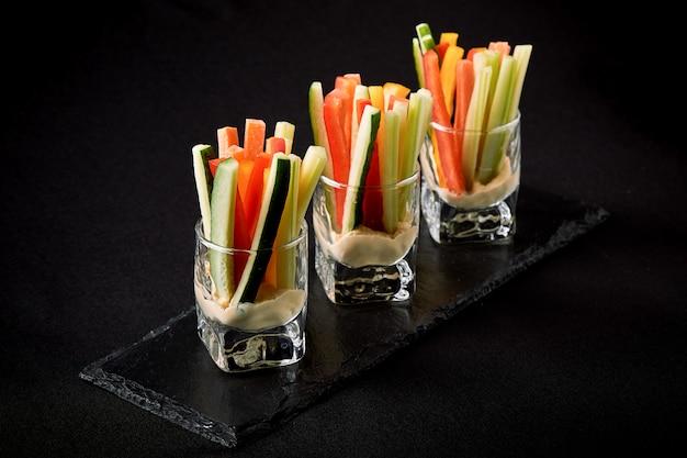 Heerlijke sappige komkommers, wortels, selderij, in dunne reepjes of clubs gesneden, worden in een glasglas als tussendoortje geserveerd om in een pikante saus te duiken. het concept van het fusievoedsel, rustig, exemplaarruimte.