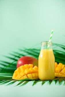 Heerlijke, sappige smoothie met oranje fruit en mango. pop-artontwerp, creatief de zomerconcept. vers sap in glazen flessen over groene palmbladeren.