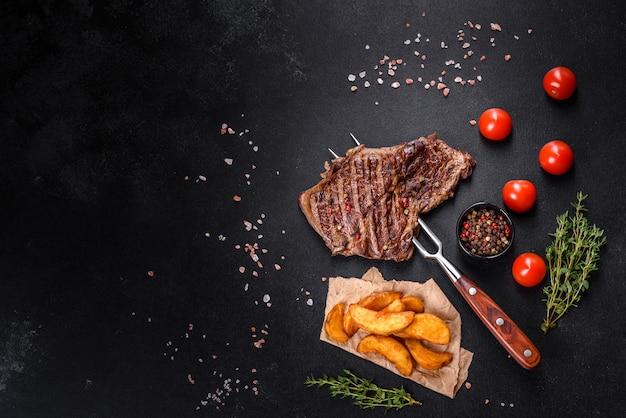 Heerlijke sappige verse biefstuk met specerijen en kruiden op een donkere betonnen ondergrond. gegrilde gerechten