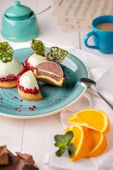 Heerlijke sinaasappel- en chocoladetaarten in het spiegelmuntglazuur op een blauw bord op een witte houten tafel in de bakkerij