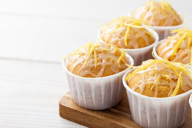 Heerlijke smakelijke oranje muffins op houten bord, kopieer ruimte, plaats voor tekst, weergave van bovenaf, witte achtergrond, horizontaal