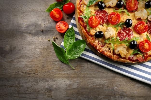 Heerlijke smakelijke pizza met ingrediënten op houten tafel