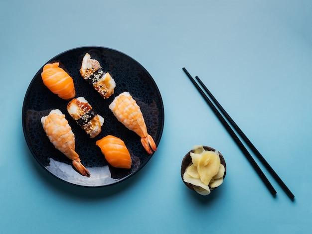 Heerlijke smakelijke sushi-set geserveerd op kleiplaat met sojasaus en eetstokjes plat op blauw