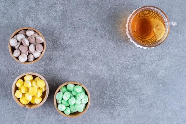 Heerlijke snoepjes en kopje thee met schijfje citroen op marmeren oppervlak