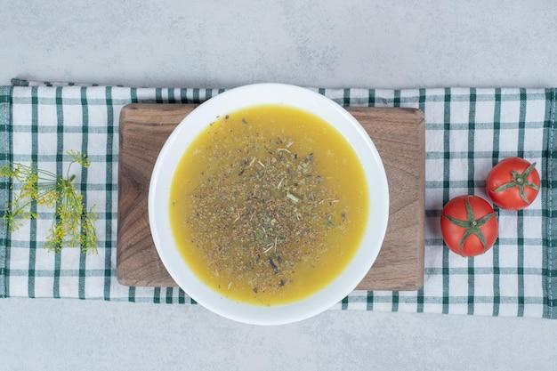 Heerlijke soep met greens en twee tomaten op tafelkleed